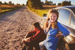 Father and daughter changing broken tire during summer rural road trip. royalty free stock photos