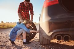 Father and daughter changing broken tire during summer rural road trip. royalty free stock photo