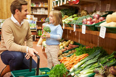 Father And Daughter Choosing Fresh Vegetables In Farm Shop Royalty Free Stock Images
