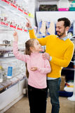 Father and daughter choosing pretty bird. Smiling father and daughter choosing pretty bird for keeping in pet shop. Focus on the girl Royalty Free Stock Images