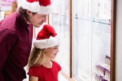 Father and daughter in Christmas attire looking at jewelry display Stock Image