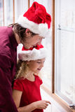 Father and daughter in Christmas attire looking at jewelry display Stock Photo