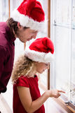 Father and daughter in Christmas attire looking at jewelry display Royalty Free Stock Photo