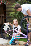 Father And Daughter Cleaning Bike Together Royalty Free Stock Image