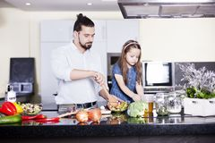 Father and daughter cooking meal together stock image