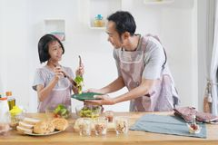 Father and daughter cooks in the kitchen at home Stock Images