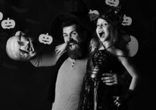 Father and daughter in costumes. Halloween party and celebration. Concept. Wizard and little witch in black hats hold pumpkin. Girl and bearded men with royalty free stock images