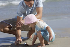 Father and daughter (2-4) crouching on beach, looking for shells, smiling, side view Stock Photos
