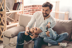 Father and daughter. Cute little girl and her handsome father are playing game console and laughing while sitting on couch at home royalty free stock photography