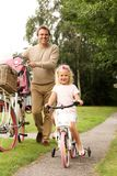 Father and daughter cycling together in park. Full length portrait of father and daughter cycling together in park stock photos