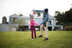 Father and daughter dancing in garden Royalty Free Stock Images