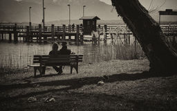 Father and daughter. Father and daugther sitting peacefully by a lake Stock Photography