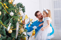 Father and daughter decorate a Christmas tree. Stock Image