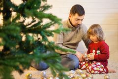 Father and daughter decorating Christmas tree. Father and daughter decorating Christmas tree together, indoors Stock Images
