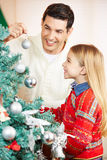 Father and daughter decorating christmas tree. Together at home Stock Photo
