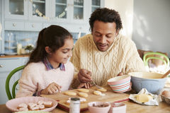 Father And Daughter Decorating Cookies At Home Together Stock Photo