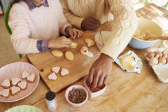 Father And Daughter Decorating Cookies At Home Together Stock Images