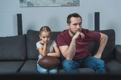 Father and daughter disappointed while watching american football game stock photos
