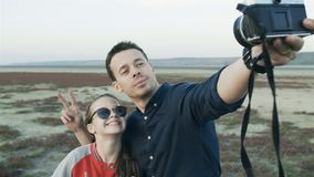 Father and daughter do selfie outdoors. Take pictures of yourself on a vintage camera. Father and daughter do selfie. Daughter climbed on her father`s back for stock video footage