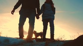 Father and daughter with a dog teamwork happy family tourists silhouette concept navigation . team dad and daughter on. Top of mountain at sunset raise walking stock video