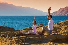 Father and daughter doing yoga exercise on the beach Stock Photography