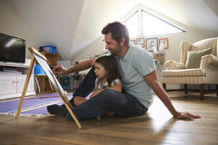 Father And Daughter Drawing On Chalkboard In Playroom Stock Photos