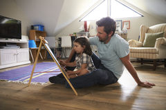 Father And Daughter Drawing On Chalkboard In Playroom Royalty Free Stock Photos