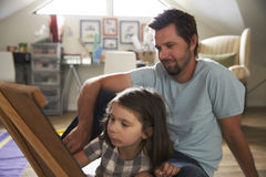 Father And Daughter Drawing On Chalkboard In Playroom Stock Photography