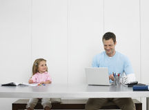Father And Daughter Drawing And Using Laptop Stock Image