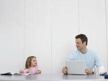 Father And Daughter Drawing And Using Laptop Stock Photos