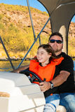 Father and Daughter Driving a Boat on a Desert Lake Stock Photography