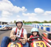 Father and daughter driving go kart on the track royalty free stock photo