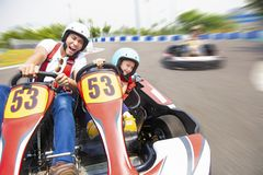 Father and daughter driving go kart on the track royalty free stock image