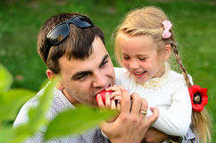 Father with daughter eating apples together. Stock Photos