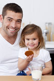 Father and daughter eating biscuits with milk Stock Images
