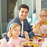 Father and daughter eating with grandfather Stock Images
