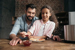 Father and daughter eating toasts with jam in kitchen Royalty Free Stock Photos