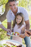 Father And Daughter Enjoying Barbeque By Lake Royalty Free Stock Photos