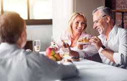 Father and daughter enjoying the meal. Delicious meal together. Happy smiling women enjoying the dish with her elderly father while celebrating and sitting in Royalty Free Stock Photography