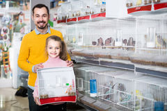 Father and daughter enjoying their purchase of canary bird in pe Royalty Free Stock Photos