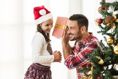 Father and daughter exchanging and opening Christmas presents Royalty Free Stock Photo