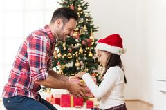 Father and daughter exchanging and opening Christmas presents Royalty Free Stock Images