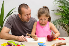 Father and daughter. A father is exercising the alphabet with his little daughter Stock Photos