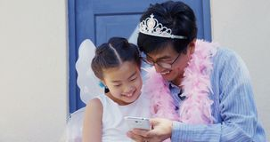 Father and daughter in fairy costume taking a selfie with mobile phone 4k. Happy father and daughter in fairy costume taking a selfie with mobile phone 4k stock video