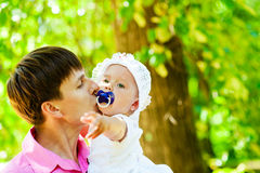 Father and daughter favorite. Daddy kisses his daughter holding hands on the Stock Image