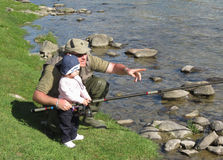 Father and daughter fishing on river Stock Photos
