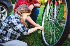 Father and daughter fixing problems with bicycle outdoor in summer. stock photo