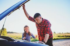 Father and daughter fixing problems with car during summer road trip. stock photos