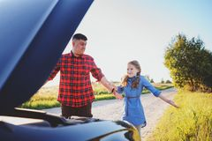 Father and daughter fixing problems with car during summer road trip. royalty free stock images