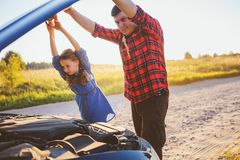 Father and daughter fixing problems with car during summer road trip. stock images